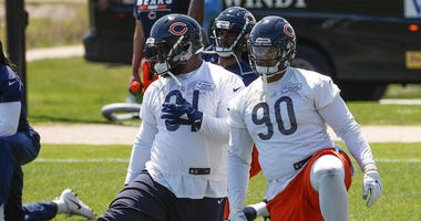 Bears defensive tackle Eddie Goldman (91) and defensive end Jonathan Bullard (90) stretch during organized team activities.