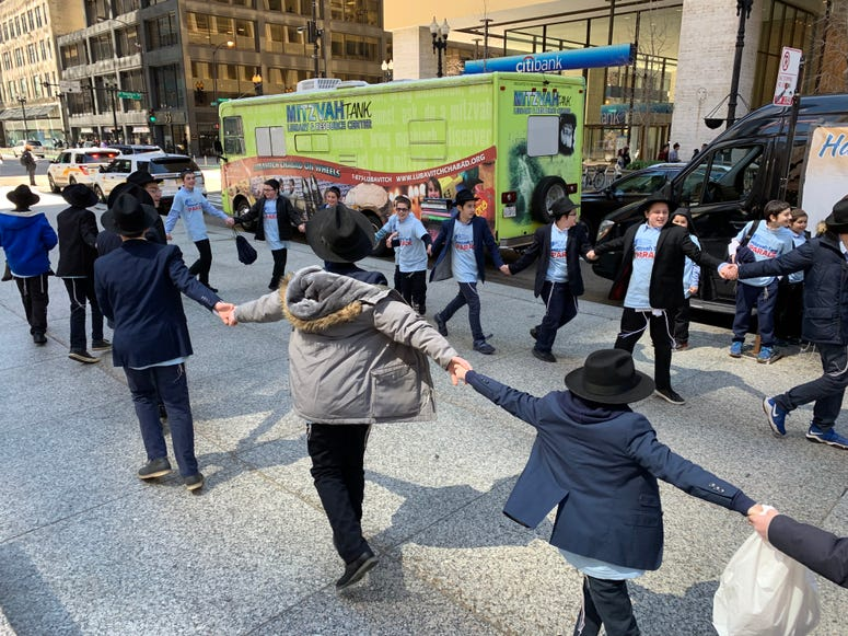 """A convoy of small buses - dubbed """"Mitzvah Vehicles"""" - drove into the Loop today at noon, before spreading out over the city to bring Passover greetings from a school in Skokie."""