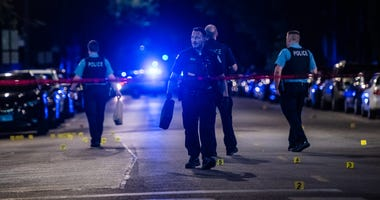 Chicago police investigate the scene where multiple people were shot, Monday night, in the 6200 block of South King Drive, in the Washington Park neighborhood.