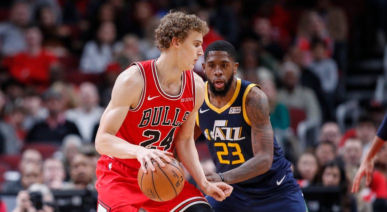 Lauri Markkanen (24) controls the ball defended by Utah Jazz forward Royce O'Neale