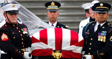 The flag-draped casket of Sen. John McCain, R-Ariz., is carried to a hearse from the U.S. Capitol in Washington, Saturday, Sept. 1, 2018, in Washington, for a departure to the Washington National Cathedral for a memorial service. McCain died Aug. 25.