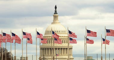 Flags fly in front of the U.S. Capitol in Washington, Tuesday morning, Jan. 1, 2019, as a partial government shutdown stretches into its third week