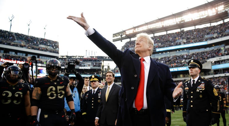 President Donald Trump tosses the coin before the Army-Navy NCAA college football game Saturday, Dec. 8, 2018