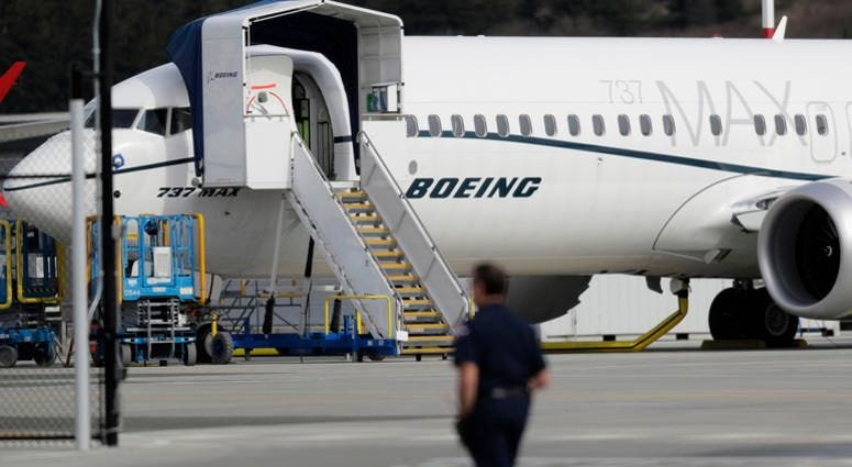 File photo, a worker walks next to a Boeing 737 MAX 8 airplane parked at Boeing Field in Seattle. U.S. aviation regulators said Monday, April 1, Boeing needs more time to finish changes in a flight-control system suspected of playing a role in two deadly