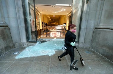 A volunteer worker walks past a shattered display window early Sunday morning, May 31, 2020, at the downtown Macy's store in Chicago, after a night of unrest and protests over the death of George Floyd, a black man who was in police custody in Minneapolis