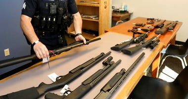 In this May 23, 2018, photo, Seattle Police Crisis Response Team Sgt. Eric Pisconski displays guns seized from people deemed to be a danger to themselves or others.