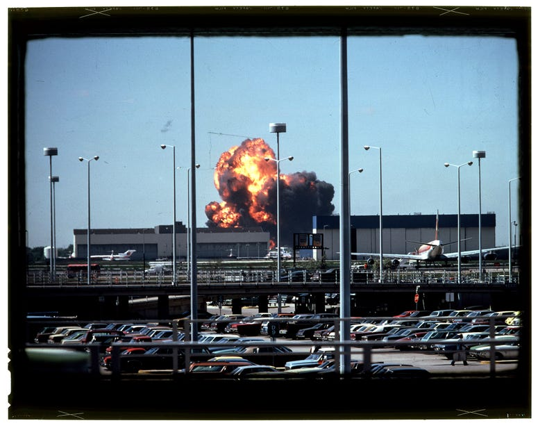 Beneath the smoke lie fragments of the American Airlines Flight 191 jetliner that crashed and exploded on May 25, 1979, shortly after taking off from O'Hare International Airport. All aboard perished.