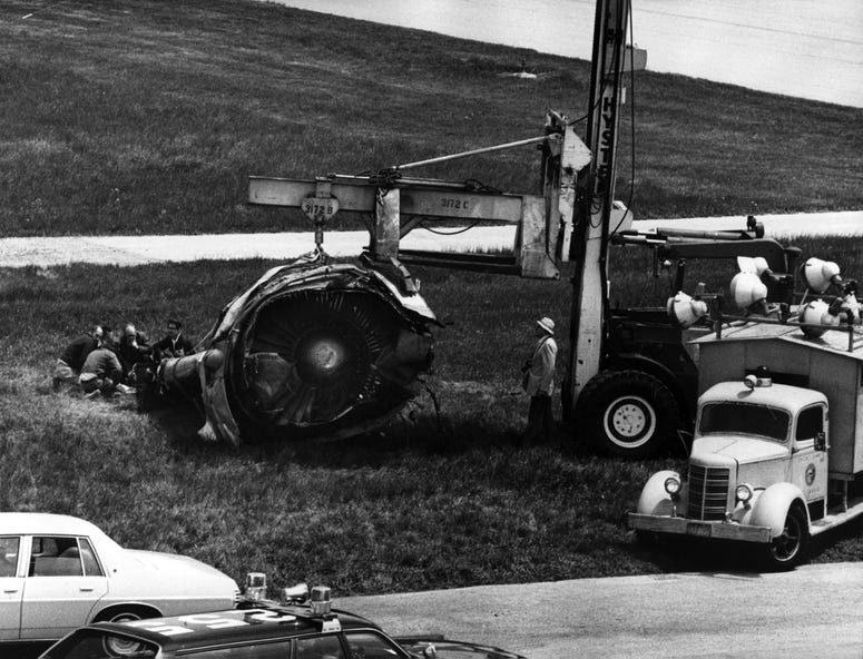 The DC-10 engine lays on the grass just east of Runway 32, right, where it stopped after falling from American Airlines Flight 191, just as the plane rotated from the runway, May 26, 1979. Investigators examine the engine.