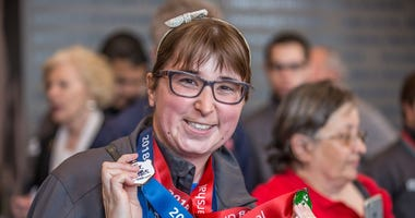 Allison Berggren shows off her medals at a Special Olympics event.