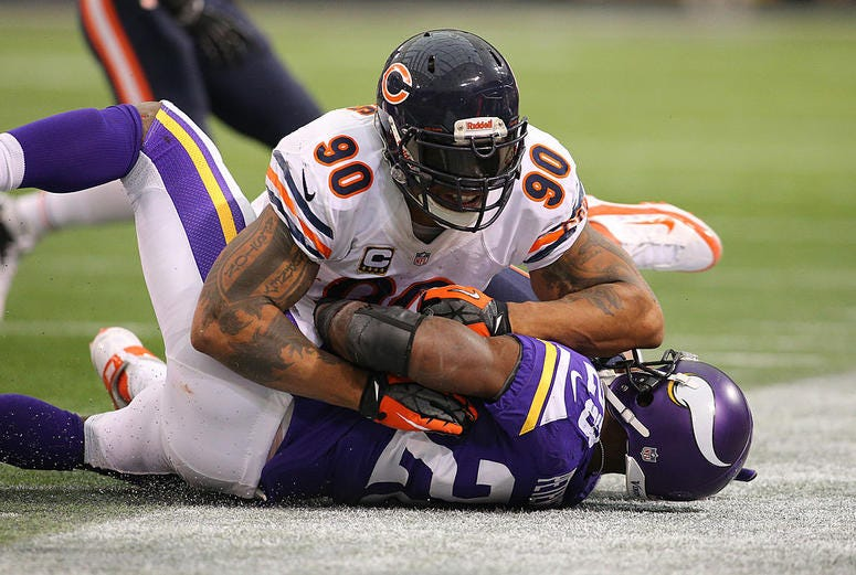Adrian Peterson #28 of the Minnesota Vikings is tackled by Julius Peppers #90 of the Chicago Bears on December 1, 2013 at Mall of America Field at the Hubert Humphrey Metrodome in Minneapolis, Minnesota.