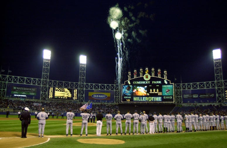 Members of the New York Yankees watch as fireworks explode over Comiskey Park before a game against the Chicago White Sox in Chicago, Illinois.