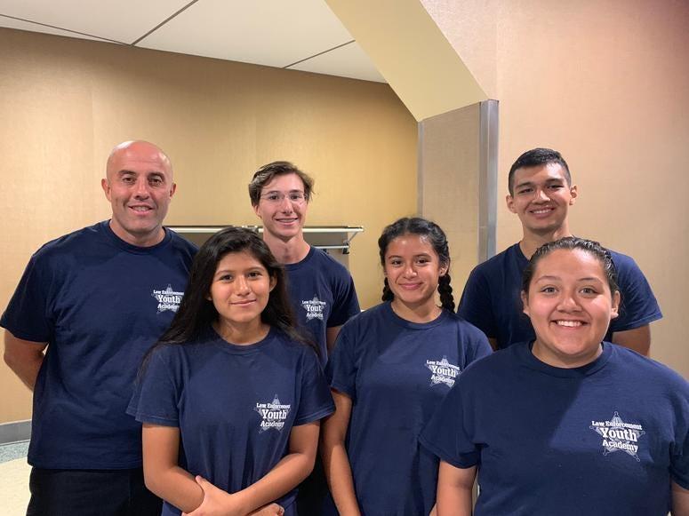 Front row: Suzie Gonzalez, Melody Gonzalez, Elizabeth Morales; Back row: Officer Daniel Gray, Kyle Rasmussen, Jose Vasquez Jr.