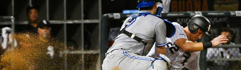 Chicago White Sox's Charlie Tilson (22) scores past Toronto Blue Jays catcher Danny Jansen during the eighth inning of a baseball game Thursday, May 16, 2019, in Chicago.