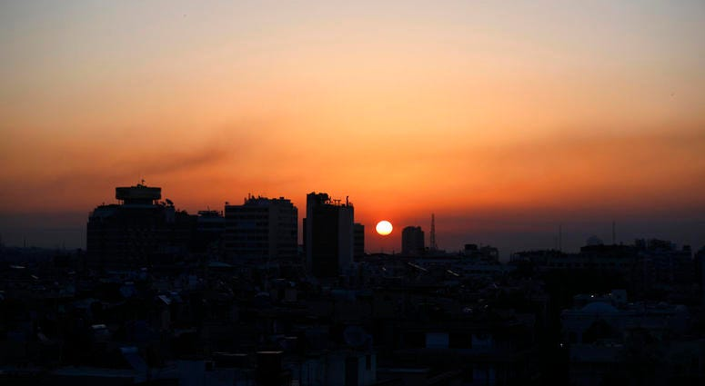 Smoke rises at sunrise after airstrikes targeting different parts of the Syrian capital Damascus, early Saturday, April 14, 2018. Syria's capital has been rocked by loud explosions that lit up the sky with heavy smoke.