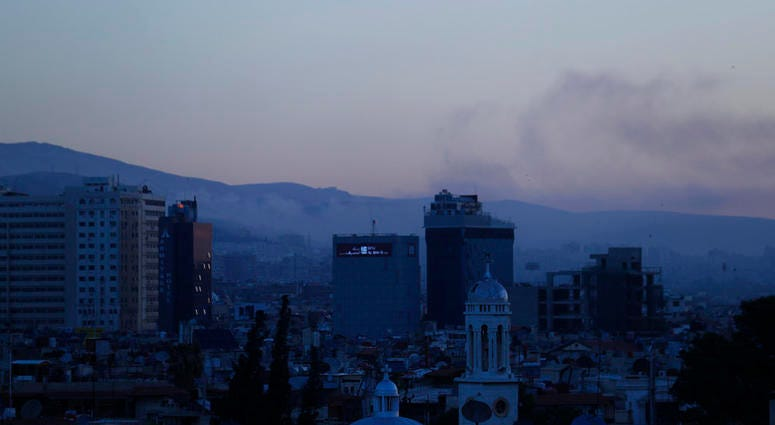 Smoke rises after airstrikes targeting different parts of the Syrian capital Damascus, Syria, early Saturday, April 14, 2018. Syria's capital has been rocked by loud explosions that lit up the sky with heavy smoke.