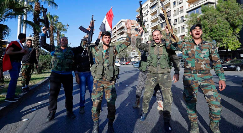 Syrian soldiers hold their weapons as they dance and chant slogans against U.S. President Trump during demonstrations following a wave of U.S., British and French military strikes to punish President Bashar Assad for suspected chemical attack against civi