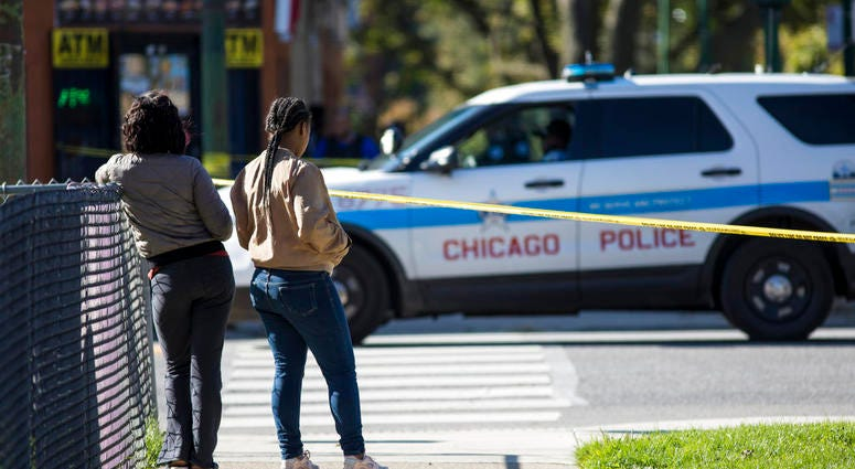 In this Monday, Oct. 22, 2018 photo, residents watch as Chicago Police investigate following a shooting after a funeral service in Chicago. Police scrambled Tuesday to ward off retaliatory attacks by street gangs after a Chicago rapper known for taunting
