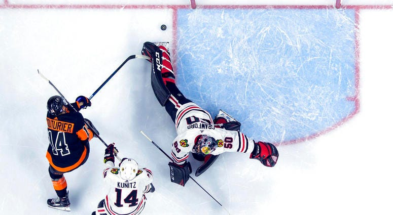 Philadelphia Flyers' Sean Couturier, left, shoots the puck past Chicago Blackhawks' Corey Crawford, right, for a goal with Chris Kunitz, center, defending during the second period of an NHL hockey game, Saturday, Nov. 10, 2018, in Philadelphia. (AP Photo/