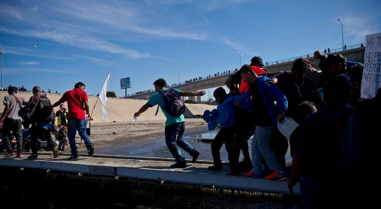 Migrants cross the river at the Mexico-U.S. border after getting past a line of Mexican police at the Chaparral crossing in Tijuana, Mexico, Sunday, Nov. 25, 2018, as they try to reach the U.S. The mayor of Tijuana has declared a humanitarian crisis in hi