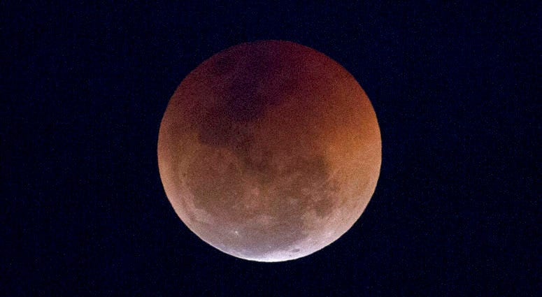 FILE - This Friday, July 27, 2018 file photo shows a blood moon lunar eclipse from the Arpoador beach in Rio de Janeiro, Brazil. Starting Sunday evening, Jan. 20, 2019, all of North and South America will be able to see the only total lunar eclipse of 201