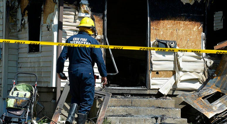 Erie Bureau of Fire Inspector Mark Polanski helps investigate a fatal fire at 1248 West 11th St. in Erie, Pa, on Sunday, Aug. 11, 2019.