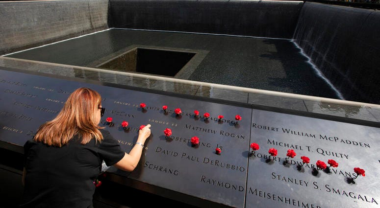 Norma Molina, of San Antonio, Texas, leaves flowers by the names of firefighters from Engine 33 at the September 11 Memorial, Monday, Sept. 9, 2019, in New York.