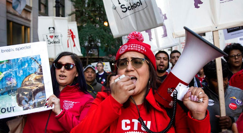 In this Oct. 14, 2019 file photo, members of the Chicago Teachers Union and SEIU Local 73 march through the Loop after a rally, three days before the unions could walk off the job on strike.