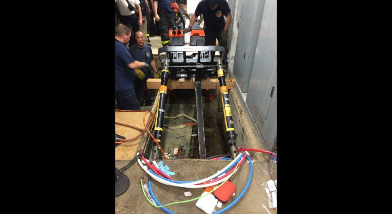 Chicago fire officials work to remove the forklift that injured a 51-year-old man Sept. 30, 2019 from a hole at the Museum of Science and Industry