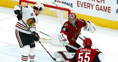 Arizona Coyotes goaltender Darcy Kuemper (35) makes a save as Chicago Blackhawks center Dylan Strome (17) looks for a rebound as Coyotes defenseman Jason Demers (55) looks on during the second period of an NHL hockey game Tuesday, March 26, 2019