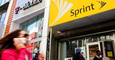 In this April 27, 2010 file photo, a woman using a cell phone walks past T-Mobile and Sprint stores in New York. T-Mobile and Sprint are trying again to combine in a deal that would reshape the U.S. wireless landscape, the companies announced Sunday, Apri