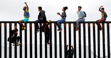 Central American migrants sit on top of the border wall on the beach in San Diego during a gathering of migrants living on both sides of the border, Sunday, April 29, 2018.