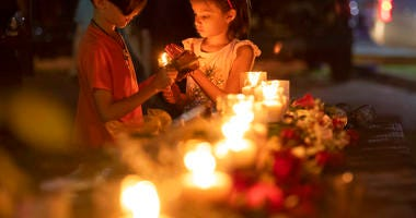 Lucrecia Martinez, 7, and her brother Luciano, 9, of Dickinson light candles during a vigil held in the wake of a deadly school shooting with multiple fatalities at Santa Fe High School on Friday, May 18, 2018, in Santa Fe, Texas