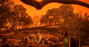 A Volkswagen Beetle scorched by a wildfire called the Carr Fire rests at a residence in Redding, Calif., Friday, July 27, 2018. The wildfire roared with little warning into the Northern California city as thousands of people scrambled to escape before the