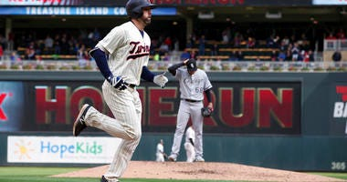 Minnesota Twins' Jake Cave jogs home on a solo home run off Chicago White Sox pitcher Dylan Covey, background, in the fourth inning of a baseball game Sunday, Sept. 30, 2018, in Minneapolis. (AP Photo/Jim Mone)