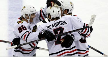 Chicago Blackhawks forward Patrick Kane, left, celebrates with defensemen Brent Seabrook and Erik Gustafsson, of Sweden, after Kane's first goal against the Columbus Blue Jackets during the third period of an NHL hockey game in Columbus, Ohio, Saturday, O