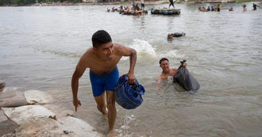 Central American migrants reach the shore on the Mexican side of the Suchiate River after wading across, on the the border between Guatemala and Mexico, in Ciudad Hidalgo, Mexico, Saturday, Oct. 20, 2018. Among the thousands of mostly Honduran migrants in