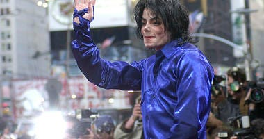 Nov. 7, 2001 file photo, Michael Jackson waves to crowds gathered to see him at his first ever in-store appearance in New York.