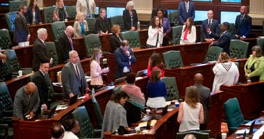 As her Democrat colleagues stand at their desks, Illinois state Rep. Kelly Cassidy, D-Chicago, makes a final plea for the Reproductive Health Act on the floor of the Illinois House chambers Tuesday, May 28, 2019, in Springfield, Ill.