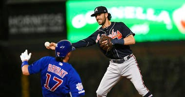 Atlanta Braves shortstop Dansby Swanson right, throws to first base after forcing out Chicago Cubs' Kris Bryant (17) at second base, on a double play hit into by Anthony Rizzo during the third inning of a baseball game Wednesday, June 26, 2019, in Chicago
