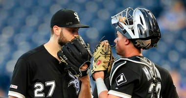 Chicago White Sox starting pitcher Lucas Giolito (27) talks with catcher James McCann (33) after a run scored in the fourth inning of a baseball game against the Kansas City Royals at Kauffman Stadium in Kansas City, Mo., Monday, July 15, 2019.