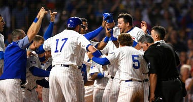 Chicago Cubs' Kyle Schwarber celebrates with teammates at home plate after hitting a solo home run to defeat the Cincinnati Reds 4-3 in the 10th inning of a baseball game Tuesday, July 16, 2019, in Chicago.