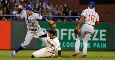 Chicago Cubs shortstop Javier Baez, left, throws to first base after forcing out San Francisco Giants' Mike Yastrzemski, center, at second base on a double play hit into by Pablo Sandoval during the fifth inning of a baseball game in San Francisco, Monday