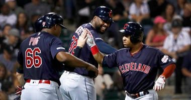 Cleveland Indians Jose Ramirez, right, celebrates with Yasiel Puig (66) and Franmil Reyes after Ramirez's three-run home run off Chicago White Sox's Hector Santiago during the third inning of a baseball game Tuesday, Sept. 24, 2019, in Chicago.