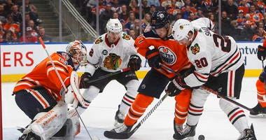Chicago Blackhawks' Brandon Saad (20) and Edmonton Oilers' Oscar Klefbom (77) battle for the rebound from Edmonton Oilers' goalie Mikko Koskinen (19) as Luke Johnson (62) skates in during third period NHL hockey action in Edmonton, Alberta.
