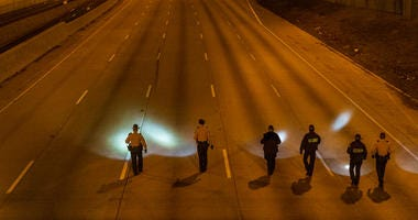 Illinois State Police walk in formation, Friday morning, on the inbound I-94 Expressway near 79th Street, looking for evidence of the shooting that left one woman wounded.