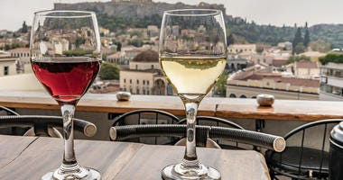 Glasses of wine with a view of the Acropolis in Athens, Greece.