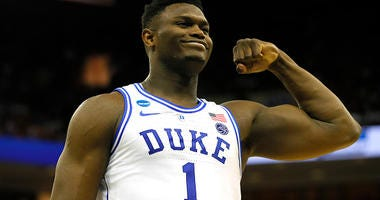 Zion Williamson flexes his muscles during a game with Duke.