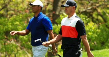 Brooks Koepka of the United States and Tiger Woods of the United States walk from the eighth tee during the first round of the 2019 PGA Championship at the Bethpage Black