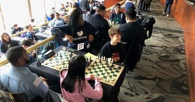 In the Stadium Club at Sox Park, with a view of the field, on a rainy day better suited for indoor activities than baseball, 150 CPS students and a couple dozen CPD officers were playing chess.