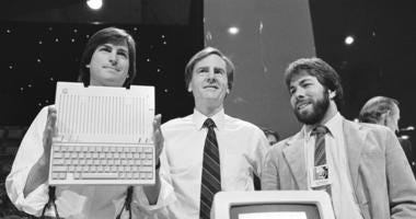 FILE - In this April 24, 1984 file photo, Steve Jobs, left, chairman of Apple Computers, John Sculley, center, president and CEO, and Steve Wozniak, co-founder of Apple, unveil the new Apple IIc computer in San Francisco, Calif.